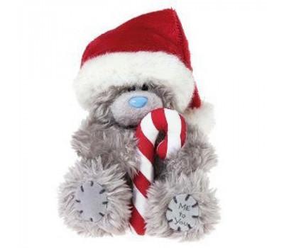 Мишка  в шапке Деда Мороза держит конфету
